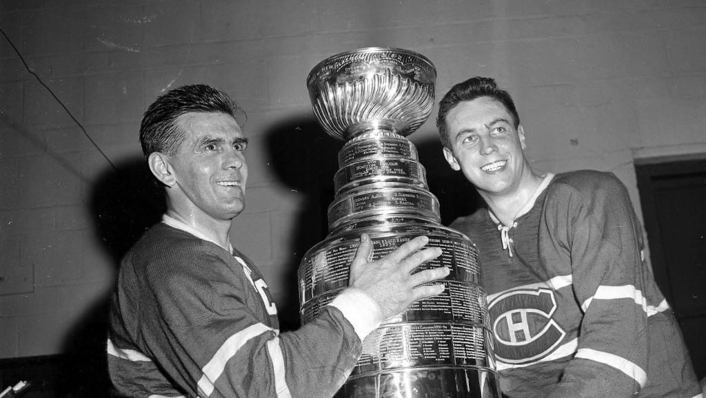 Maurice Richard (left) and Jean Béliveau, of the Montreal Canadiens smile happily in the dressing room with the Stanley Cup after defeating the Boston Bruins 5-3 at the Boston Garden on April 20, 1958. (AP Photo)